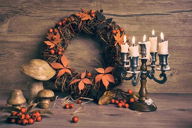 秋の花輪と古代燭台キャンドルスティック、炎のあるキャンドルのある静物。木製のキノコと木の果実。季節の誕生日や記念日カードのデザイン。