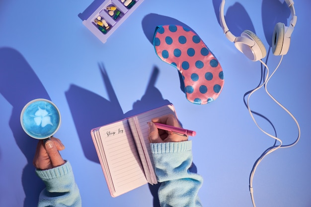 ピンクとブルーの健康的な夜の睡眠の創造的なコンセプト。睡眠マスク、緑の水玉模様のピンク、イヤホン、不安を和らげる鎮静薬、睡眠記録ノート。紫色の壁、長い影のデザイン。