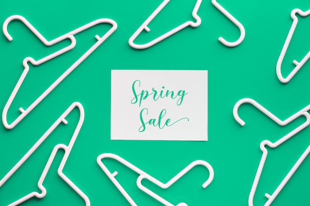 白いプラスチックハンガー、紙に「春のセール」のテキスト。トップビューフラットは、トレンディなパステルグリーンのミントの壁、幾何学的構成、創造的なミニマリズムに横たわっていた。フラットレイアウト、春のセールオンライン。