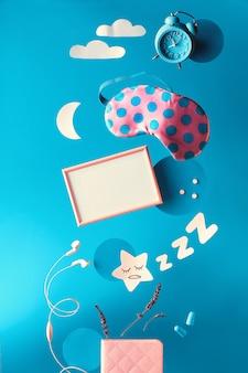Креативная концепция здорового сна, текст «оптимизация сна» на лайтбоксе. летающая или парящая спящая маска, будильник, наушники, затычки для ушей, таблетки. бумажная лунная звезда, облака