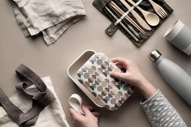 廃棄物ゼロのランチキット、コットンバッグにセットされた持ち帰り用のランチボックス、竹製のカトラリーのオーガナイザー、竹製のランチボックス、再利用可能なカップ。持続可能なライフスタイル、幾何学的なフラットレイアウト、クラフト紙の平面図。