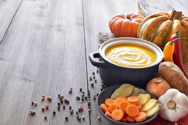 木製のテーブルの暗いセラミック鍋にカボチャ、ニンジン、生姜のクリームスープ