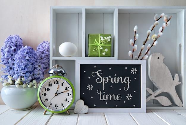 古い目覚まし時計、青いヒヤシンスの花、さまざまなオブジェクトのディスプレイキャビネット。黒板にチョークテキスト「春」