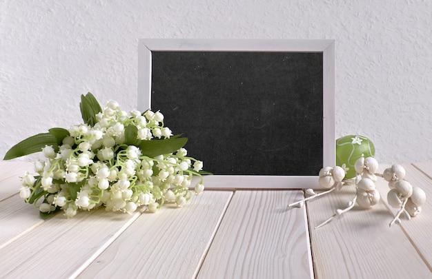 「ハッピーイースター」のテキスト、ユリの谷と白い紙の花の束が黒板