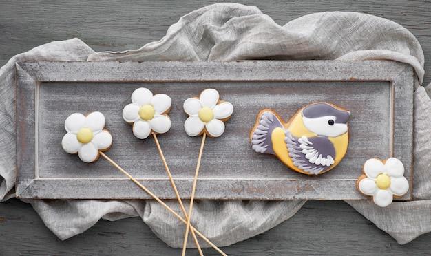 シジュウカラ鳥と灰色の木の板の上に花の形をしたジンジャーブレッド