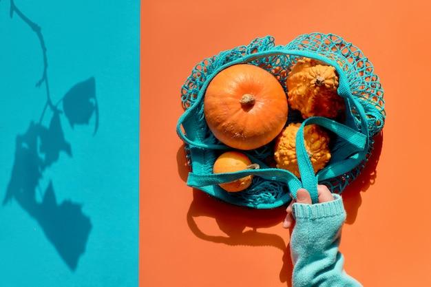 秋のフラットレイアウト、一致する分割紙にオレンジ色のカボチャとターコイズブルーの文字列バッグを保持している青いセーターを手に