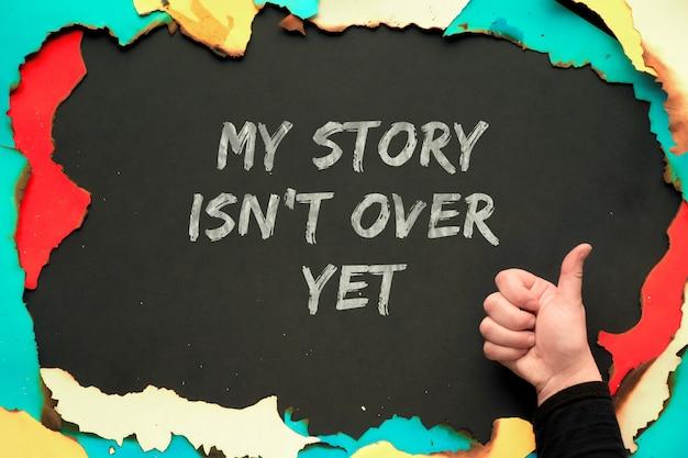 Моя история еще не закончена, текст на черной бумаге в обожженной бумажной рамке со знаком