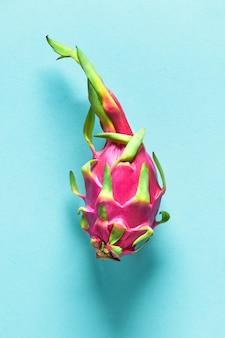 青いミントの背景に新鮮な有機ピンク、白、緑のドラゴンフルーツ(ピタヤまたはピタハヤ)と創造的なフラットなレイアウト。平面図、全体の新鮮な健康的なフルーツのフラットレイアウト。