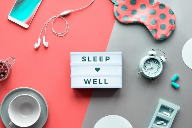 Текст «спи спокойно» на модном лайтбоксе. таблетки, капсулы и успокаивающий чай. плоская планировка, оранжевый коралловый и серебряный фон. коралловая маска для сна с горошком, будильником, наушниками и затычками для ушей.
