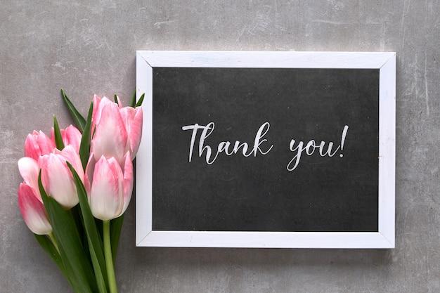 黒板にピンクのストライプの白いチューリップのテキスト「ありがとう」の挨拶、灰色の石の上に平らに置く