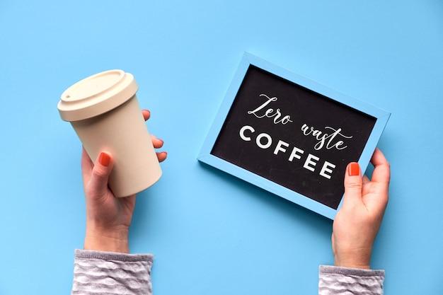 Бамбуковая чашка кофе, держать чашку или кружку в женской руке на фоне голубой мяты. творческая плоская планировка, изображение, текст «ноль отходов кофе» на доске. экологически чистая чашка для путешествий без отходов.