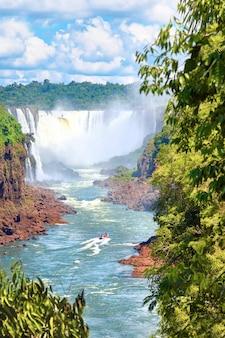 Водопады игуасу в аргентине. туристическая моторная лодка идет к мощному водному каскаду, создающему туман над рекой игуасу. пышная листва субтропического дождевого леса.