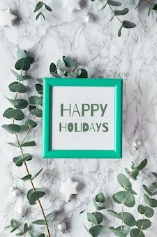 Текст «счастливых праздников» в зеленой рамке. рождество, новогодняя зимняя рамка со свежими эвкалиптовыми ветками и белыми черными безделушками, безделушки со звездами. плоская планировка, вид сверху на фоне белого мрамора.
