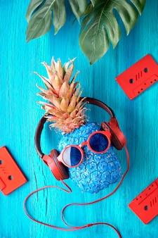 ターコイズブルーの木材にサングラス、赤いオーディオテープ、エキゾチックな葉のパイナップル