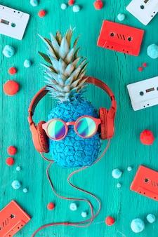 パイナップルとサングラス、ターコイズブルーのウッドのイヤホン、オーディオテープ