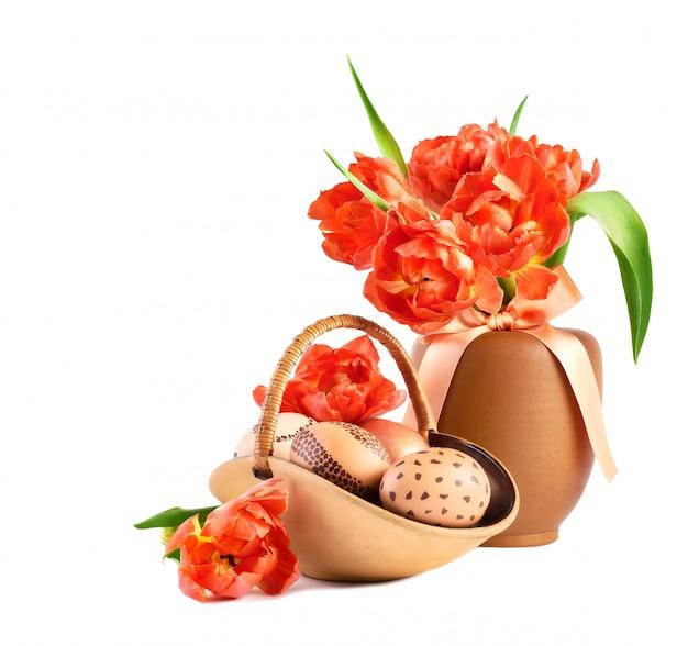 Корзина пасхальных яиц и букет оранжевых тюльпанов в фарфоровой вазе