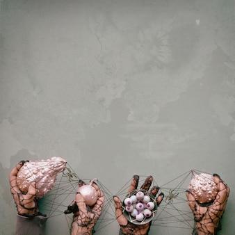 Творческий фон хэллоуин. руки в черных сетчатых перчатках с розовыми декоративными тыквами и шоколадными глазками. руки связаны с черной нитью в кошачьей колыбели с пауками.