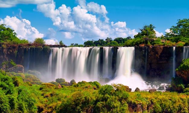Водопады игуасу в аргентине. панорамный вид нескольких мощных водных каскадов, создающих туман над рекой игуасу, проходящей через субтропический тропический лес.