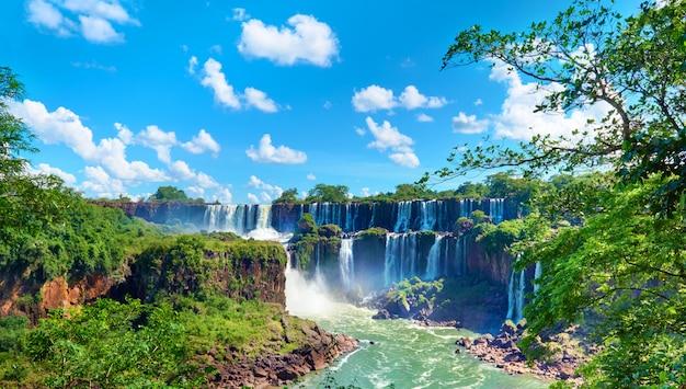 Водопады игуасу в аргентине, мощные водные потоки, создающие туман над рекой игуасу. панорамное изображение водопадов и субтропических дождевых лесов в долине реки.