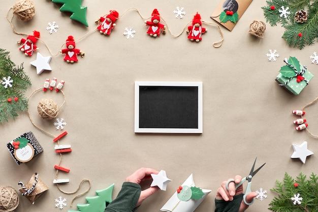 コピースペースで無駄のないクリスマスフレーム。クラフトペーパーのフラット横たわっていた、トップビュー。繊維小物、常緑樹、紙ギフトボックスを手に。環境に優しいクリスマス。コピースペース、テキストを黒板に配置します。