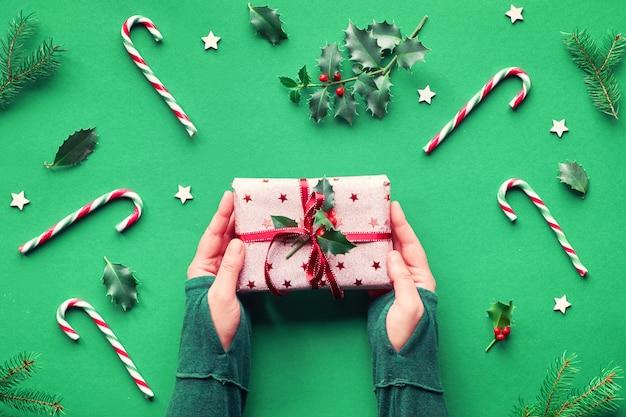 トレンディなクリスマスフラットはキャンディー杖、ホリーとモミの小枝、木製の星、ガラスの装身具と緑の紙の背景に横たわっていた。ピンクの包装紙に包まれたギフトボックスを保持している女性の手。