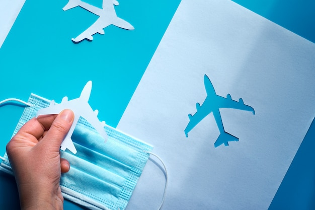 飛行を再開し、隔離を終了します。フェイスマスクの上に紙飛行機を持っている手は、影から光へと導きます。空の旅は旅行の後で再開します。パンデミック。