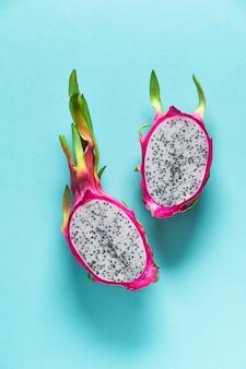 青の新鮮な有機ピンクドラゴンフルーツと創造的なフラットなレイアウト
