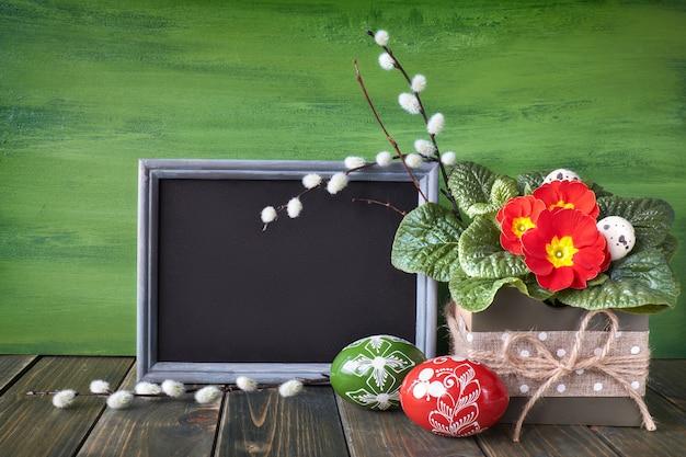 塗装イースターエッグと素朴な木製の背景に赤いプリムローズポット花とイースターバスケット