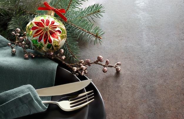 Рождественская концепция меню с украшенными черными тарелками и столовыми приборами