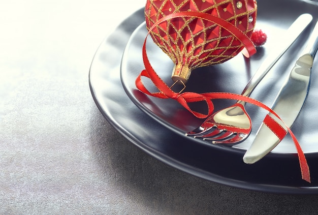 Рождественское меню с черными тарелками и столовыми приборами, украшенными лентами и безделушками