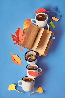 ノートブック、コーヒー、秋の葉で秋の計画を立てる上での創造的な概念
