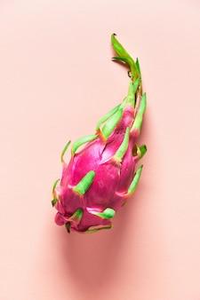 コーラルカラーの用紙の背景に新鮮な有機ピンク、白、緑のドラゴンフルーツと創造的なフラットなレイアウト。トレンディなトップビュー、全体の新鮮な熟した健康的なエキゾチックなフルーツのフラットレイアウト。