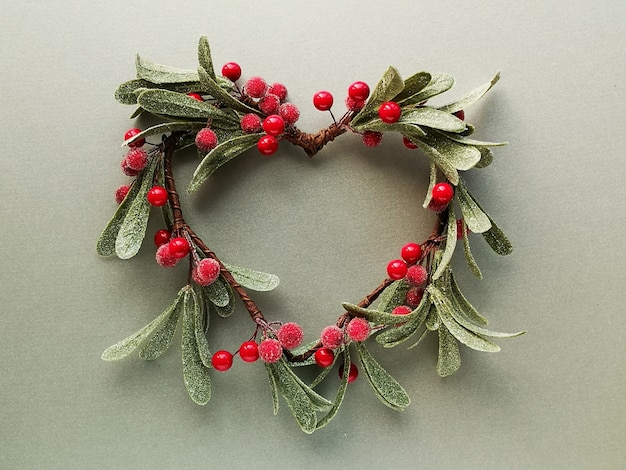 つや消しの葉と赤い果実がハートの形をした装飾的なヤドリギの花輪。メタリックグリーンペーパーのフラットレイアウト、トップビュー。