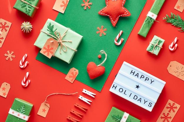 赤と緑のクリスマス背景。環境にやさしいゼロ廃棄物のクリスマス正月飾り。幾何学的なフラットレイアウト、ギフト、ボックス、テキスト付きライトボックス