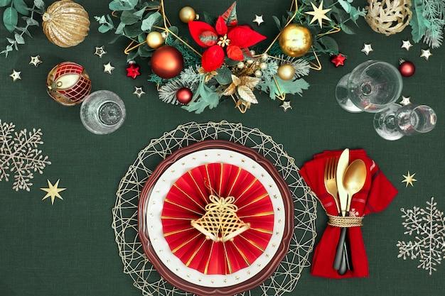 Рождественская сервировка в золотых, бордовых и синих тонах. плоская планировка, вид сверху на декоративную раскладку стола, золотые столовые приборы, белые тарелки со звездами, традиционный декор на темно-зеленом белье