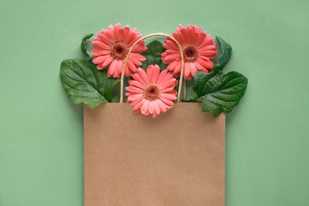 Цветы ромашки коралловые герберы в хозяйственной сумке на зеленой бумаге