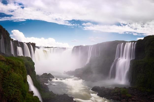 Водопады игуасу в аргентине, вид изо рта дьявола. панорамный вид многих величественных мощных водных каскадов с туманом и низкими облаками. ,