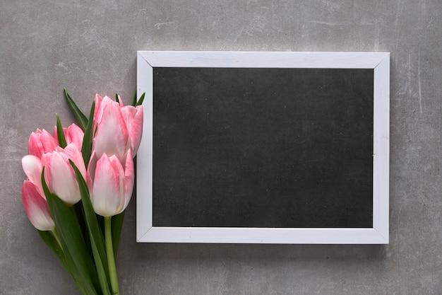 「母の日おめでとう!」ピンクのストライプの白いチューリップと黒板に、平らな灰色の石の上に置く