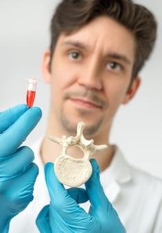 科学者は、手袋をはめた手で脊椎と赤い液体の入ったチューブを保持しています。