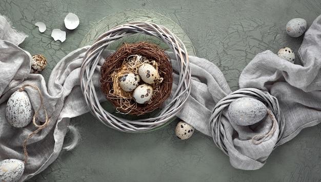 Пасхальная квартира лежала на темном фоне с перепелиными яйцами в гнезде, льняной фабрикой и двумя золотыми яйцами на темном