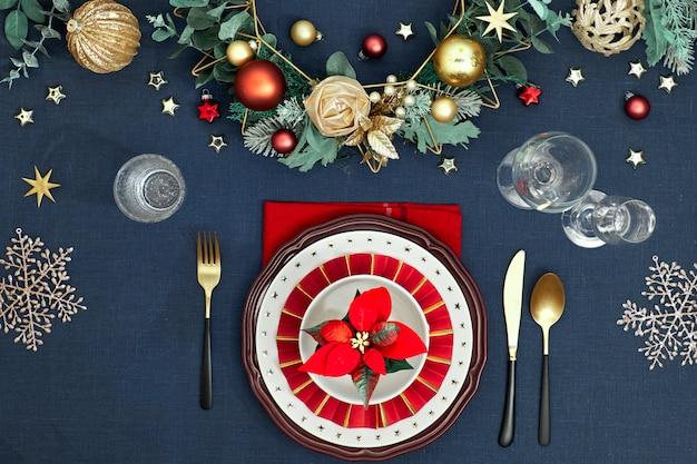 Рождественская сервировка в золотых, бордовых и классических синих тонах. вид сверху на декоративный стол макет, золотые столовые приборы, белые тарелки со звездами. традиционный рождественский декор на классическом синем льне