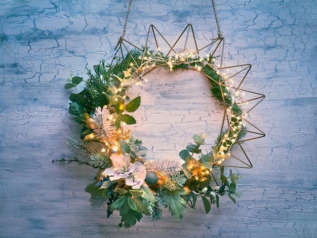 モミ、冬の葉、ライトガーランドと幾何学的な金色の金属フレームの花の装飾的なクリスマスリース