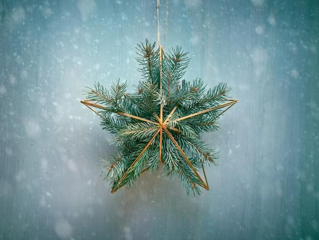 モミの小枝と黄金の幾何学的な星のクリスマスリースは、素朴な木、伝統的なクリスマス飾りに掛かります。無駄のないシンプルな装飾
