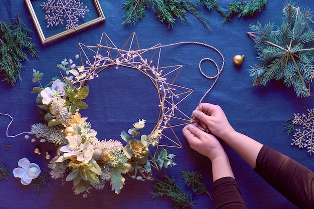 古典的な青いリネンの装飾的なクリスマスリースの作成。女性の手は手作りの花輪を作る。クリスマスの装飾。