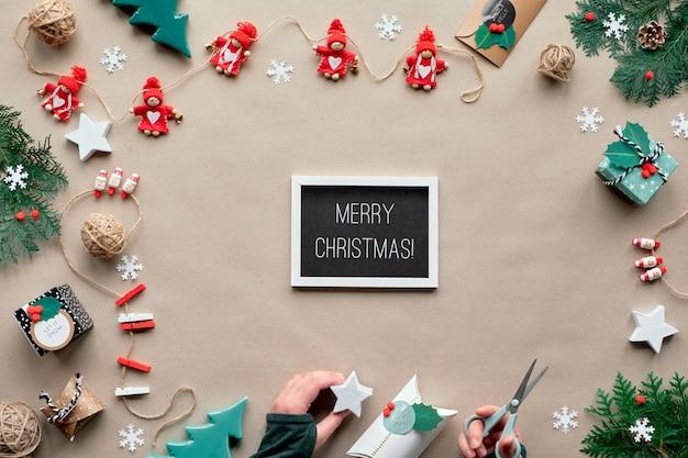 創造的な手作りの装飾、無駄のないクリスマスフレーム。テキスタイル装身具、手。環境にやさしいフラットレイアウト、テキストメリークリスマス