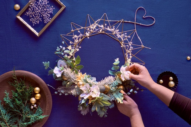 古典的な青いリネンの装飾的なクリスマスリースの作成。女性の手は手作りの花輪を作る。