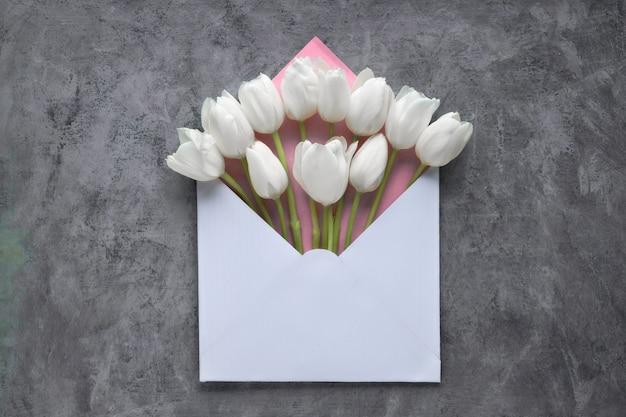 暗いフラットテクスチャ背景に封筒の春フラットレイアウト、白いチューリップ、