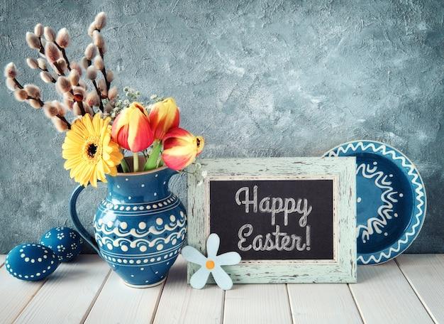 マッチングプレートとイースターエッグと黒板と青いセラミックピッチャーの春の花。