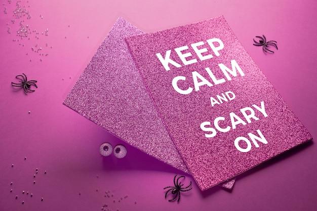 Творческий фиолетовый стол на хэллоуин с пауками, шоколадными глазами и двумя сверкающими открытками с надписью «сохраняйте спокойствие и страшно»