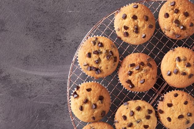 Свежеиспеченные кексы с шоколадной крошкой охлаждения на проволочной сетке на темные.